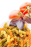 Bowl of raw pasta with basil and tomatoes Stock Image