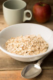 Bowl of Raw Porridge Oats on Wooden Background Royalty Free Stock Photo