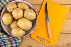 Bowl with raw potatoes, towel, chopping board and knife Royalty Free Stock Photo