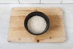 Bowl with raw rice. On wooden board Stock Photography