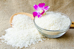 Bowl of raw Thai jasmine rice and wooden ladle Royalty Free Stock Photo