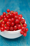 Bowl of red currant on a blue wooden background, close-up Royalty Free Stock Image