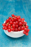 Bowl of red currant on a blue wooden background, vertical Royalty Free Stock Photography