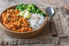 Bowl of red lentil curry with white rice and broccoli. On the wooden table Royalty Free Stock Photo