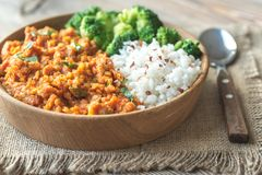 Bowl of red lentil curry with white rice and broccoli. On the wooden table Royalty Free Stock Photography