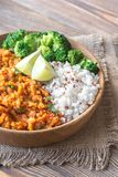 Bowl of red lentil curry with white rice and broccoli. On the wooden table Royalty Free Stock Image