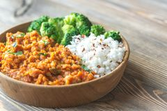 Bowl of red lentil curry with white rice and broccoli. On the wooden table Stock Photography