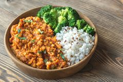 Bowl of red lentil curry with white rice and broccoli. On the wooden table Stock Photo