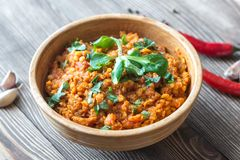 Bowl of red lentil curry. On the wooden table Stock Photos