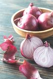 Bowl of red onions. On the wooden background royalty free stock images