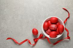 Bowl with red painted Easter eggs on table, top view. Space for text stock photo