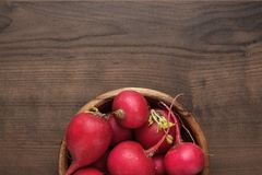 Bowl of red radishes. Fresh red radishes in wooden bowl on the brown table with copy space Royalty Free Stock Images