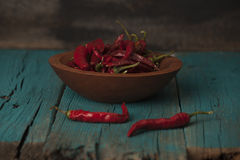 Bowl of red ripe peppers on dark background Stock Photo