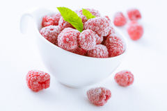 Bowl of refreshing raspberries. Bowl of refreshing frozen raspberries covered in frosting for a delicious healthy dessert, tilted closeup angle Stock Photo