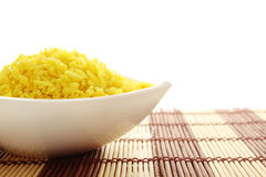 Bowl of Rice. Boiled yellow rice boiled in white bowl. Plate stands on a wooden mat. Isolated on a white background royalty free stock images