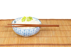 Bowl of rice with chopsticks against white backgrond Royalty Free Stock Photos