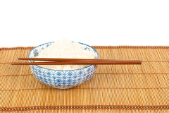 Bowl of rice with chopsticks and table mat against white backgro Stock Photos