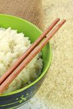 A bowl of rice and a pile of uncooked rice Stock Image