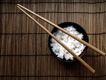 A bowl of rice representing a staple in Asian food. A bowl full of rice with two chopsticks on natural wooden background representing a staple in Asian food Stock Image