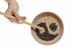 Bowl with rice. Yin and Yang. Bowl of rice in Yin and Yang symbol. And hand with chopstics adding last grain of rice Stock Photo