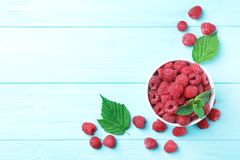 Bowl with ripe aromatic raspberries on wooden table. Top view Stock Images
