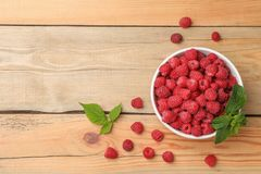 Bowl with ripe aromatic raspberries on wooden table. Top view Royalty Free Stock Photo