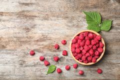 Bowl with ripe aromatic raspberries on wooden table. Top view Royalty Free Stock Photos