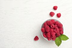 Bowl with ripe raspberries on wooden table, top view. Bowl with ripe aromatic raspberries on wooden table, top view Stock Photo