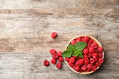 Bowl with ripe raspberries on wooden table, top view. Bowl with ripe aromatic raspberries on wooden table, top view Royalty Free Stock Photo