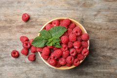 Bowl with ripe raspberries on wooden table, top view. Bowl with ripe aromatic raspberries on wooden table, top view Stock Photos