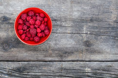 Bowl of ripe red raspberries on wooden table in summer.  Stock Photo