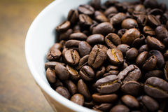 Bowl of Roasted Coffee Beans on a Wood Surface Royalty Free Stock Photography