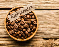 Bowl of Robusta coffee beans. Over an old wooden table Royalty Free Stock Photos
