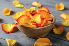 Bowl with rose petals. On wooden background royalty free stock image