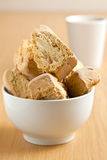 Bowl of rusks with a mug of coffee. A white bowl of rusks with a mug of coffee in the background Royalty Free Stock Photos