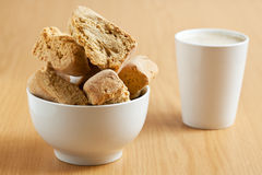 Bowl of rusks with a mug of coffee. A white bowl of rusks with a mug of coffee in the background Royalty Free Stock Images