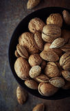 Bowl of rustic walnuts and almonds Stock Photo
