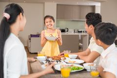 Bowl of salad. Asian girl with a bowl of salad standing in front of family dinner table Royalty Free Stock Image