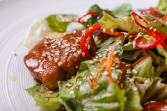 Bowl of salad with beef teriyaki and vegetables. Asian food. Salad on a white dish on table. restaurant menu stock images