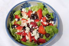 Bowl of salad. Bowl of boston lettuce, strawberries, red grapes and feta cheese Stock Image