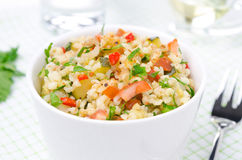 Bowl of salad with bulgur, zucchini, tomatoes, chili peppers Royalty Free Stock Image