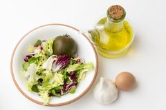 Vegetables in bowl, garlic and egg with oil. Bowl with salad, oil, garlic head and egg Royalty Free Stock Photography