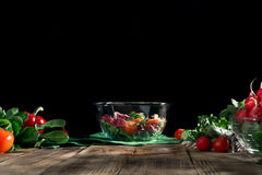 Bowl of salad on wooden board on dark background Royalty Free Stock Images