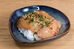 Bowl with salmon sashimi seasoned with black and white sesame, rocket, nori seaweed fried on a bed of steamed white rice. Wooden table background royalty free stock photos