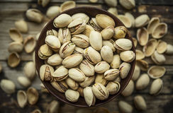 Bowl with salty pistachios in a wooden bowl on a background of shells , top view ,close up. Bowl with salty pistachios in a wooden bowl on background of shells stock photography