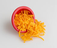 Bowl of shredded sharp cheddar cheese spilling on cutting board Stock Photos