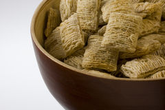 Bowl of shredded wheat cereal. A wooden, round, bowl of shredded wheat cereal (dry, no milk), white copy space Stock Images