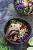 Beef with rice, red cabbage and broccoli. Bowl with sliced beef steak, broccoli, red cabbage, broccolli sprouts and satay sauce stock photography