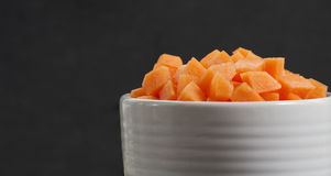 Bowl sliced carrots over black cutting board Royalty Free Stock Photo