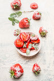 Bowl with sliced strawberries sprinkle with powdered sugar on white wooden background Stock Photo